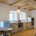 Kuchyňa v zrekonštruovanej chalupe s pracovnou linkou v dreve, modrou retro chladničkou a oblúkovými nikami s oknami