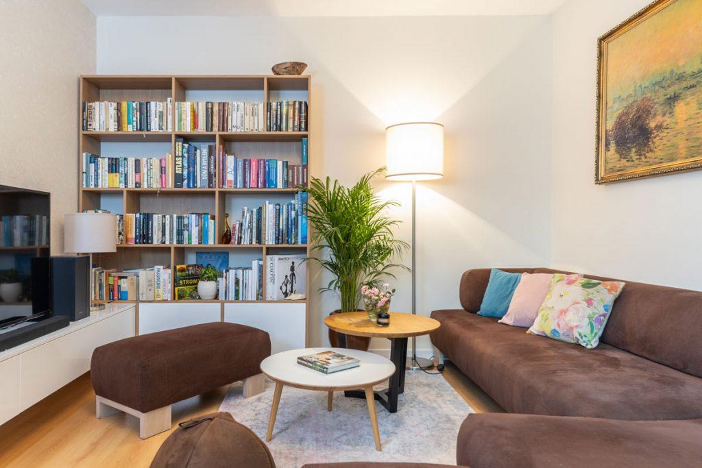 obývačka s hnedou čalúnenou sedačkou, okrúhlymi stolíkmi, závesnou skrinkou v lesklej bielej farbe a knižnicou