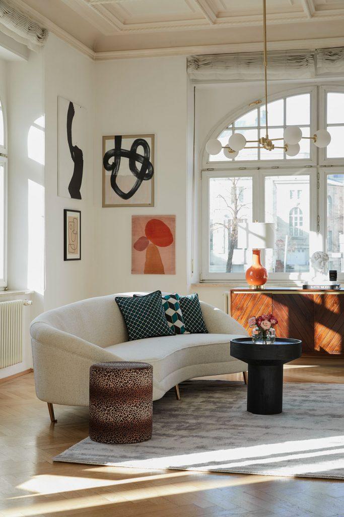 Moderná obývačka s dizajnovou sedačkou v svetlej farbe, taburetkou s leopardím vzorom, čiernym stolíkom a kobercom v metalickom vzhľade