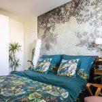romantická spálňa s čalúnenou posteľou s obliečkami s motívom vtákov a rastlín, so staroružovým retro kreslom, s retro nočným stolíkom s dizajnovou zlatou lampou a tapetou na stene so vzorom stromov
