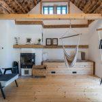 obývačka v chalupe s drevenou podlahou, francúzskym oknom, drevenými trámami, krbom a závesnými textilnými hojdačkami