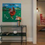 chodba s kovovou policou, zlatou dizajnovou lampou v tvare hríbika a moderným obrazom s motívom kohúta