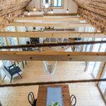 Otvorený priestor strechy v chalupe, kde z podkrovia vidieť do obývačky na prízemí