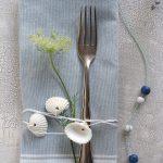 Vidlička s obrúskom previazaná stuhou s mušľami