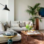obývačka v zemitých tónoch, s krémovou sedačkou, hnedým kobercom a preskleným modrým okrúhlym stolíkom v tvare presýpacích hodín
