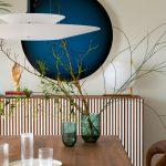 detail interiéru s tmavomodrou okrúhlou nástennou dekoráciou, pásikovou skrinkou s dizajnovým svietidlom a sklenenými modrými vázami na jedálenskom stole