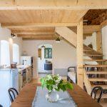 kuchyňa s dreveným jedálenským stolom, malou svetlomodrou retro chladničkou, drevenou kuchynskou linkou s opáleným drevom a schodiskom do podkrovia