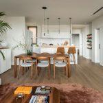 Pohľad do modernej kuchyne s dreveným jedálenským stolom a dizajnovými stoličkami a bielou kuchynskou linkou s ostrovom a barovými stoličkami