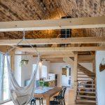kuchyňa v chalupe so závesnou hojdačkou, jedálenským stolom, kuchynskou linkou s opáleným drevom, drevenými trámami a schodiskom vedúcim do spálne