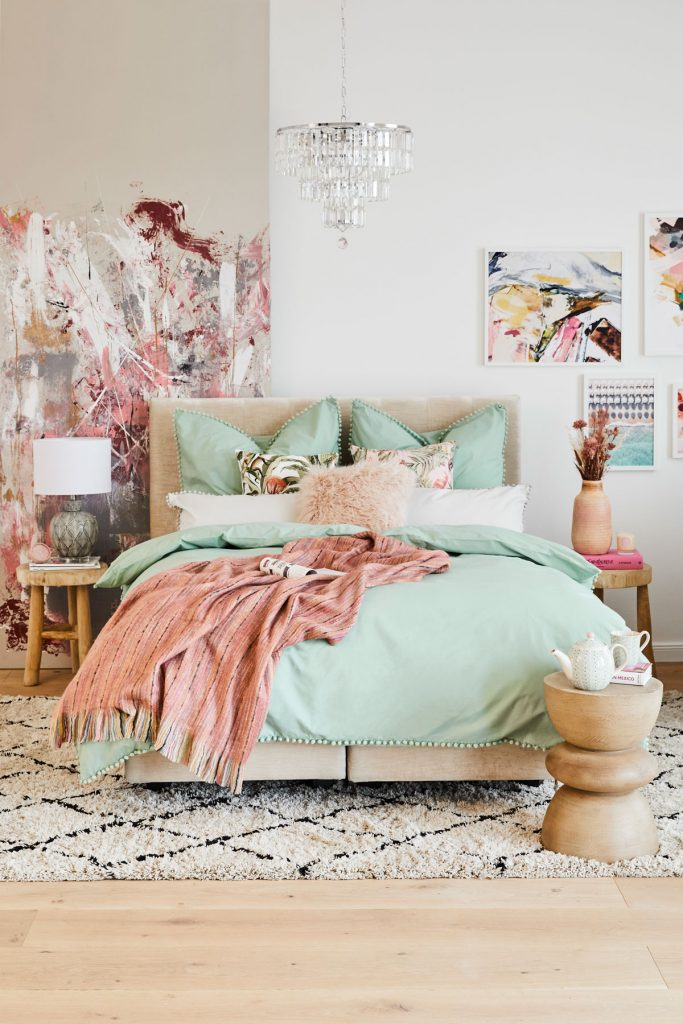 Spálňa s čalúnenou posteľou a mentolovými obliečkami, so vzorovaným kobercom, abstraktnými maľbami a vzorovanou tapetou