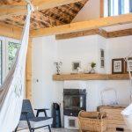 obývačka v chalupe s kozubom, retro kreslom a opáleným dreveným obkladom na strope