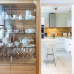 Presklená vitrína s riadmi a pohľad do kuchyne na rohovú kuchynskú linku s ostrovčekom