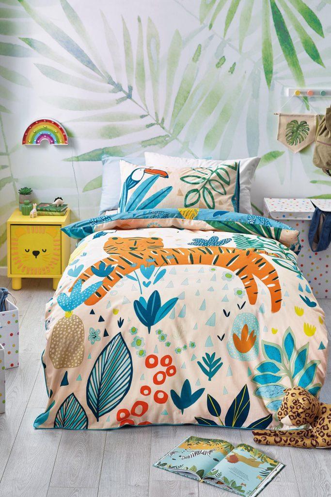 Posteľ v detskej izbe so vzorovanými obliečkami s motívom džungle a vzorovanou tapetou na stene