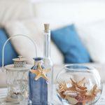 Dekorácie z modrej fľašky s pripevnenou hviezdicou na jej hrdle a lastúry s hviezdicami v okrúhlej akvarijnej nádobe