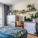 spálňa s čalúnenou posteľou a pracovným kútikom v drevodekore a bielej a s množstvom izbových rastlín
