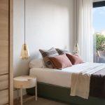 spálňa v zemitých tónoch, s tmavosivou drevenou posteľou, kobercom, svetlým okrúhlym nočným stolíkom a sklenenými visiacimi svietidlami