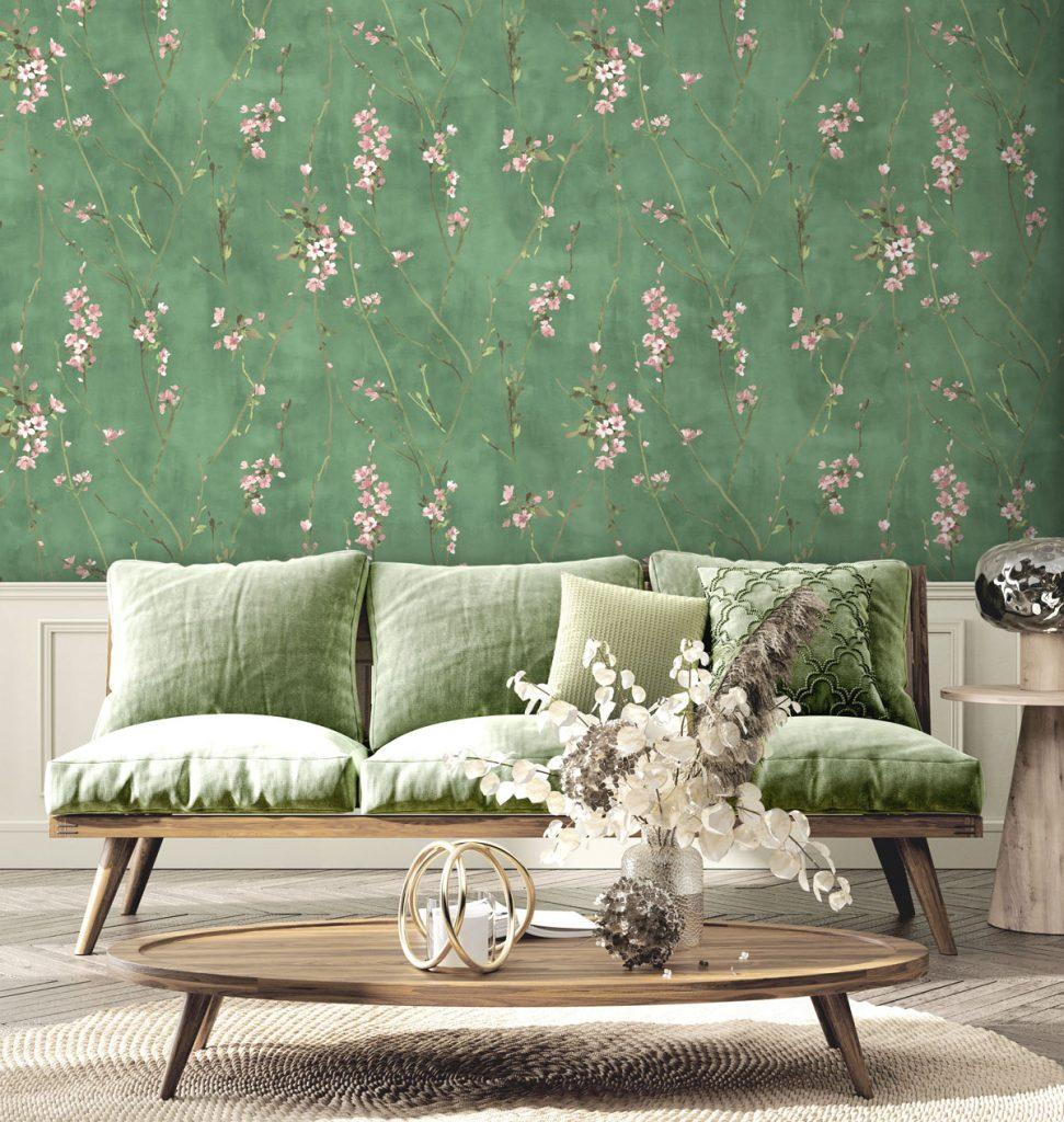 Obývačka s oválnymi dreveným stolíkom, prírodným kobercom, zelenou sedačkou a zelenou tapetou so vzorom lúčnych kvetov