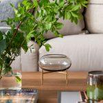 detail stola v obývačke s vázou so zeleňou a oválnou sklenenou nádobou na zlatých nožičkách