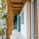 priečelie chalupy s bielou fasádou, drevenými trámami s prístreškom a tyrkysovými okenicami