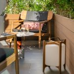 balkón so živým plotom, dizajnovými drevenými kreslami a dizajnovým dreveným lampášom