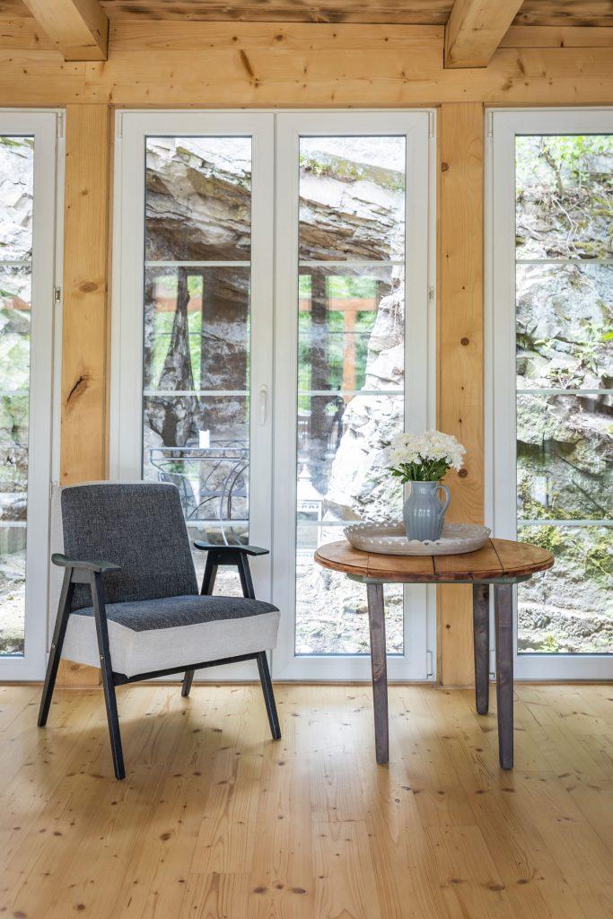 relaxačný kútik v chalupe s kreslom a dreveným stolíkom s výhľadom na skalný previs