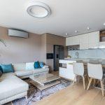 otvorený priestor obývačky a kuchyne s jedálnou v béžových a smotanových odtieňoch a lesklou kuchynskou linkou