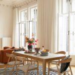 Jedáleň spojená s obývačkou, drevený stôl a dizajnové drevené stoličky, pásikavý čierno-biely koberec