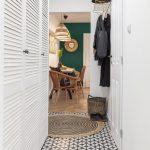 chodba v bielej farbe vedúca do obývačky, s dlažbou v čierno-bielej kombinácii, okrúhlym jutovým kobercom a zlatou nástennou policou