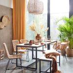 Jedáleň v prírodnom štýle so svetlým stolom s kovovou podnožou, vypletanými stoličkami s kovovou podnožou a vypletaným lustrom