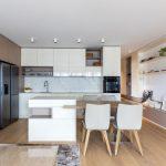 priestor modernej kuchyne s jedálenským stolom a ostrovom v smotanovej a béžovej farebnosti, s lesklou linkou a otvorenými policami
