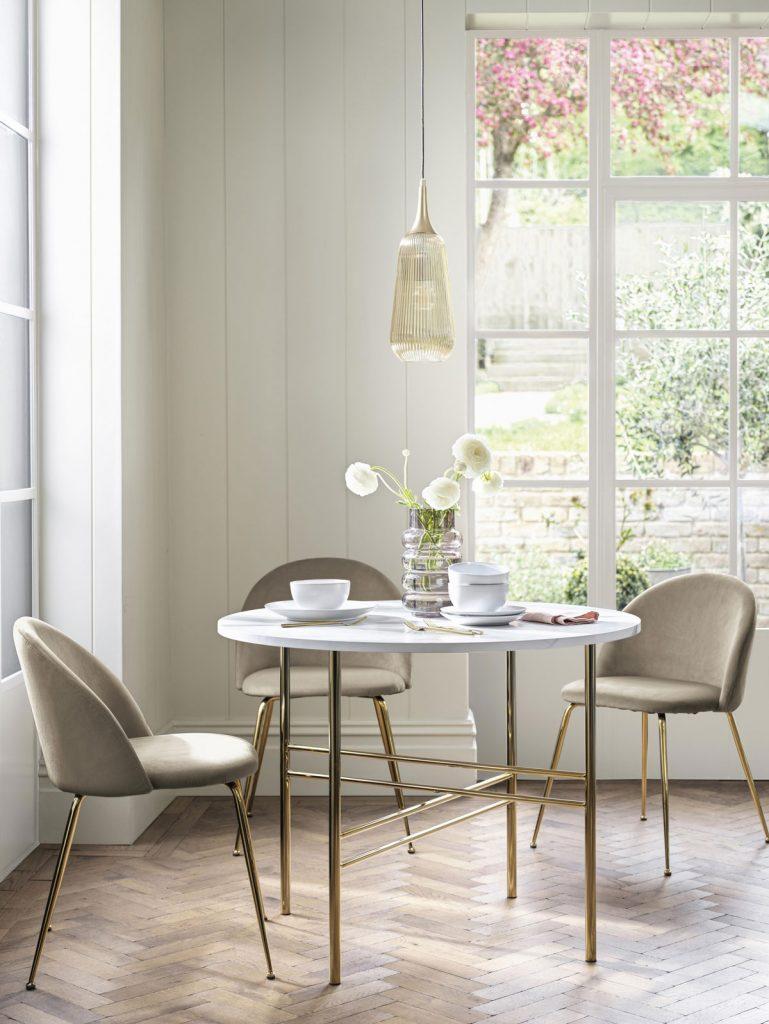 Okrúhly stôl so zlatými nožičkami a kožené jedálenské kresielka so zlatými nožičkami