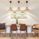 jedálenský kút v prírodnom etno štýle s dreveným stolom, koženými stoličkami, prútenými kreslami a prútenou trojicou lustrov