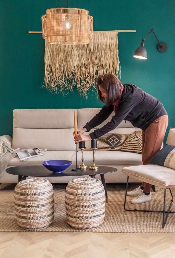 žena dekoruje obývačku v etno štýle zlatými svietnikmi