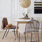 Drevený stôl a čierne kovové jedálenské stoličky s prevesenou kožušinou