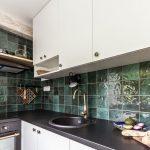 etno kuchynská linka v bielej farbe s čiernou pracovnou doskou, čiernou rúrou na pečenie a smaragdovým obkladom