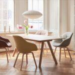 Drevený jedálenský stôl a čalúnené jedálenské kresielka v pastelových farbách