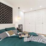 spálňa v etno štýle s veľkými bielymi šatníkovými skriňami, dreveným obrazom, čiernym dekorovaným stolíkom a posteľou so smaragdovými obliečkami