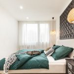 spálňa v etno štýle s dreveným obrazom a zelenými obliečkami