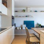 béžovo smotanová moderná kuchyňa s otvorenými policami, ktoré smerujú cez obývačku až po vstup do bytu