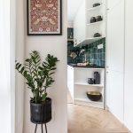 prechod do kuchyne s bielou kuchynskou linkou, smaragdovým obkladom, zošikmenými otvorenými policami a laminátovou podlahou imitujúcou parkety
