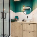 kúpeľňa s drevenou skrinkou vo svetlom dreve, čierno-bielou dlažbou, sprchovým kútom s čiernym orámovaním dverí a smaragdovou stenou