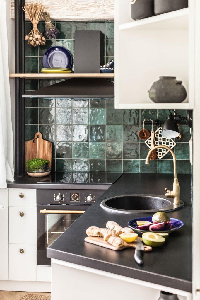 detail kuchynskej linky s čiernou pracovnou doskou, zlatou batériou a smaragdovým obkladom na zástene