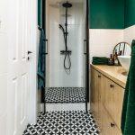 kúpeľňa s drevenou skrinkou vo svetlom dreve, čiernou-bielou geometrickou dlažbou, sprchovacím kútom s čiernym orámovaním dverí, čiernou sprchovou súpravou a smaragdovou farbou na stene aj doplnkoch