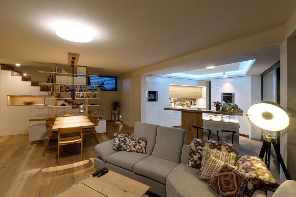 otvorený priestor modernej kuchyne s obývačkou, jedálňou a schodiskom na druhé podlažie