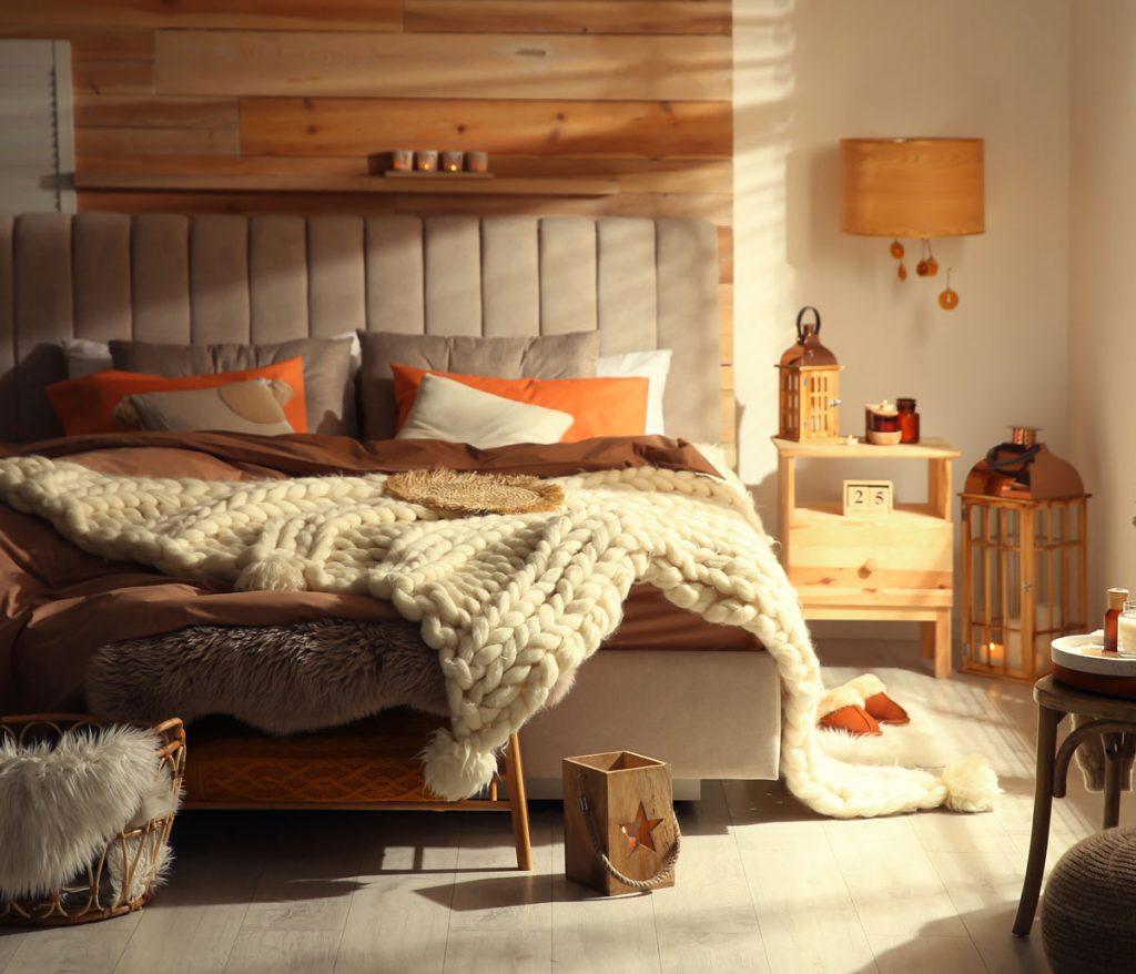 útulná spálňa s jesennou atmosférou s posteľou na ktorej je prehodená pletená deka