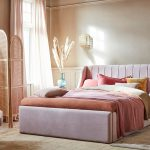 spálňa v pastelových farbách ružovej, fialovej a červenej, s prírodnými doplnkami ako ratanový paraván, vypletané svietidlo či pampová tráva