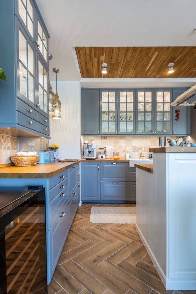 sivá kuchynská linka s drevenou pracovnou doskou, ktorej vzor da objavuje aj na strope miestnosti, retro vinotéka a kuchynský ostrovček
