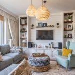 obývačka s romantickou toskánskou atmosférou, s mentolovým kreslom, sivou sedačkou s poťahom z menčestru, orientálnym pufom a bielou obývačkovou stenou s otvorenými policami, bielym dreveným obkladom za televízorom a nariasenými závesmi pri vstupe na terasu