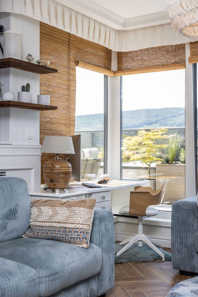 detail pracovného kútika umiestneného v rohu obývačky, s bielym stolom, drevenou stoličkou a ratanovými roletami