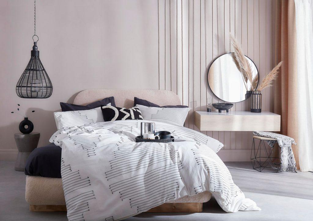 spálňa v neutrálnych tónoch s bielymi a čiernymi textíliami na posteli, béžovou stenou na ktorej je naťahaný špagát